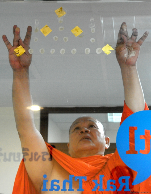 A Thai monk blesses a new business.